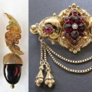 Brooch of the Victorian period. Garnets, a pearl seed, gold. Brushes hanging on a chain